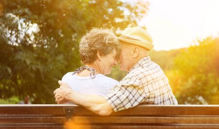 Amorous couple of seniors is sitting together in the park on a park bench in autumn