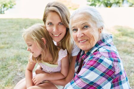 Senior woman as grandmother together with her daughter and granddaughter in summer