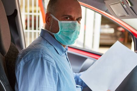Senior with face mask during coronavirus epidemic while driving a car with a blank sheet of paper as copy space