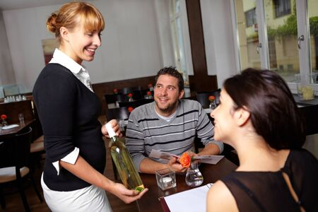 Wine waitress in the restaurant offers a bottle of white wine