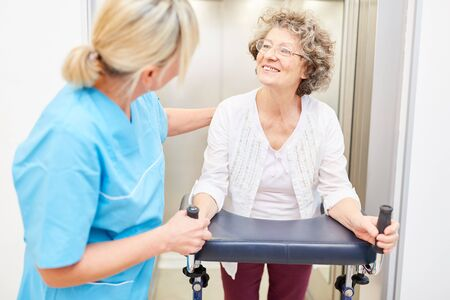 Senior with walker in geriatric care or rehab with nurse in nursing home