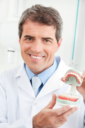Smiling dentist shows a real denture