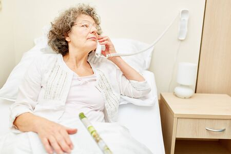 Woman as a patient makes a phone call in the hospital bed at the nursing home or hospital