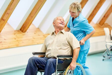 Happy senior in a wheelchair and his caring nurse in the nursing home Stockfoto