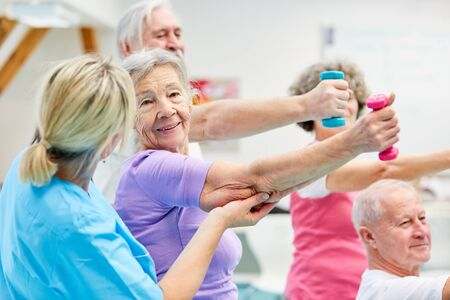 Senior group does rehabilitation in physiotherapy and trains with dumbbells