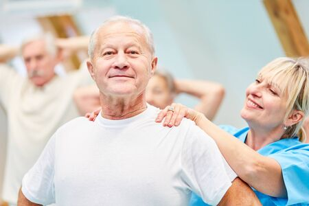 Therapist supports senior man in healthy back training Stockfoto
