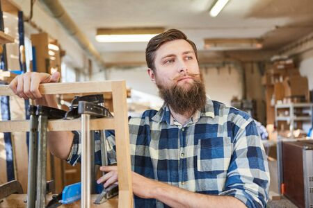 Hipster Carpenter as an independent craftsman in his carpentry