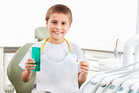 Laughing child at the dentist uses mouthwash Archivio Fotografico