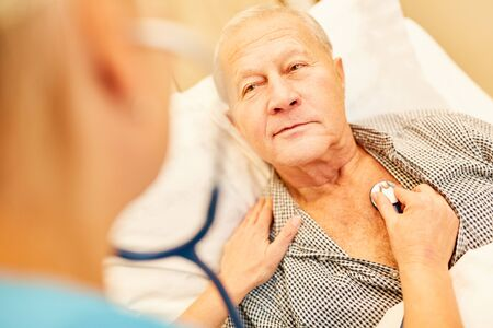 Senior as a patient is examined with the stethoscope to control breathing Banco de Imagens
