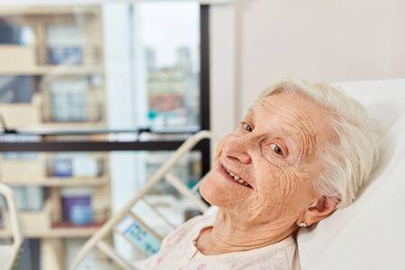 Smiling senior citizen in hospital bed in nursing home or hospital Stock Photo