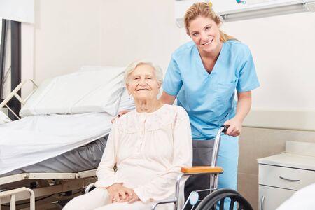 Nurse and senior woman in wheelchair at hospital or nursing home