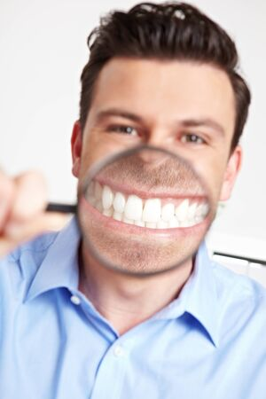 Grinning man in the office with a magnifying glass over his mouth Stock Photo