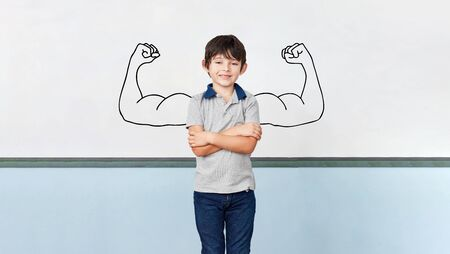 Child as a student with arms crossed in front of muscles on blackboard in school