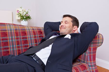 Businessman smiling relaxed lying on a sofa