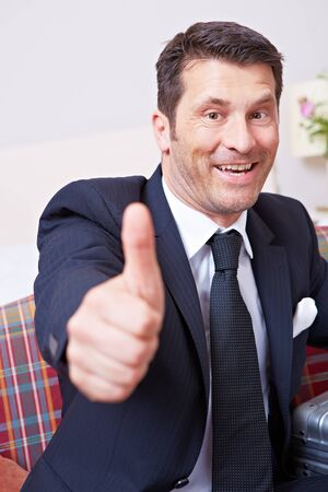 Laughing businessman holds thumbs up on sofa with suitcase