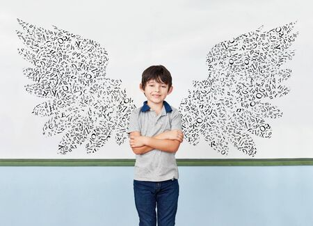 Pupils in front of blackboard with wings of letters as success and motivation concept