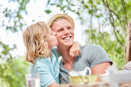 Son kisses his father lovingly on the cheek in the morning at the breakfast table Stockfoto
