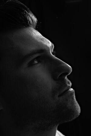 Attractive man in the dark looks up 写真素材