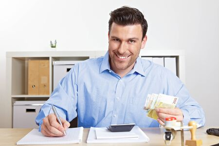 Laughing business man with banknotes in the office