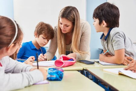 Student doing homework Mentoring in elementary school with a teacher