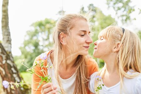 Mother and daughter look at each other lovingly and pick flowers in the garden