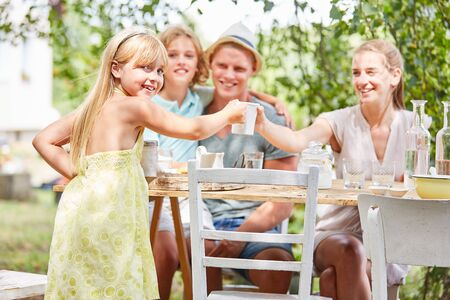 Blonde girl having coffee in the garden with family in summer