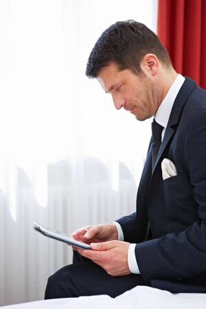 Businessman in hotel room working on tablet computer on bed