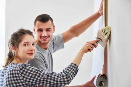 Young handyman couple wallpapering the wall with woodchip wallpaper during renovation 版權商用圖片