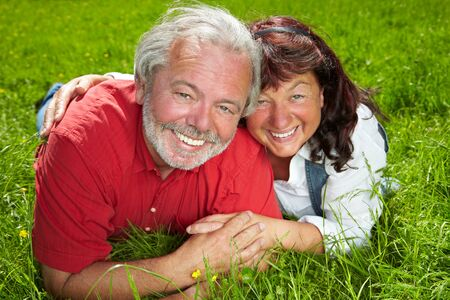 Two happy laughing seniors are lying on a green meadow