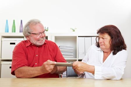 Two seniors at the table argue about a tablet computer
