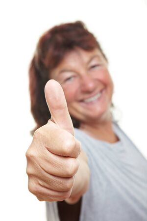 Elderly laughing woman holds her thumb up