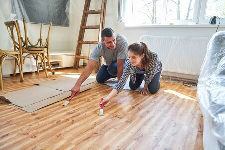 Young couple at the parquet floor paint in the new apartment as a home improvement work Standard-Bild