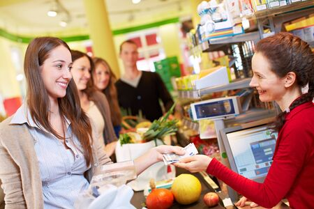 Smiling woman pays at the checkout in the supermarket Imagens