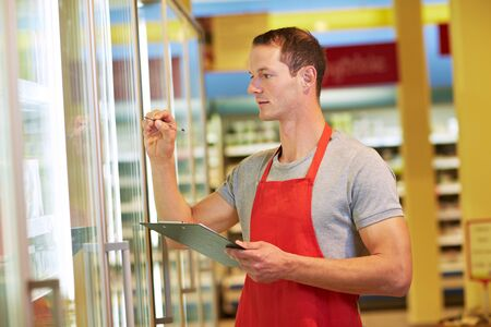 Employee checks inventory in the refrigerated section of the supermarket