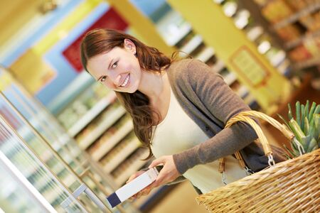 Smiling attractive woman in the supermarket with frozen food