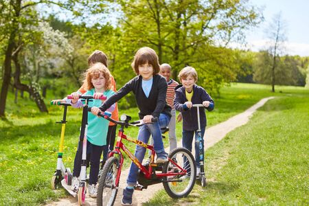 Group of kids with bike and scooter on a trip in summer in the park Stockfoto