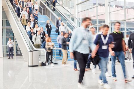 Many anonymous blurred people on escalator in mall or trade fair