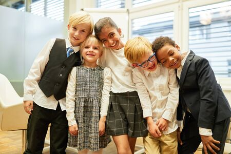 Multicultural group of laughing children as a business team in the office