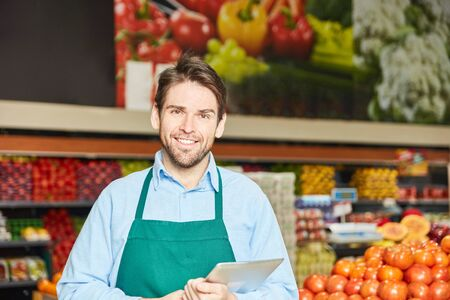Smiling man as a salesman or market leader with apron in the supermarket
