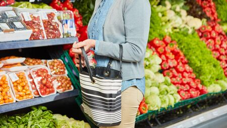 Woman hides strawberries in her handbag while shoplifting in the supermarket