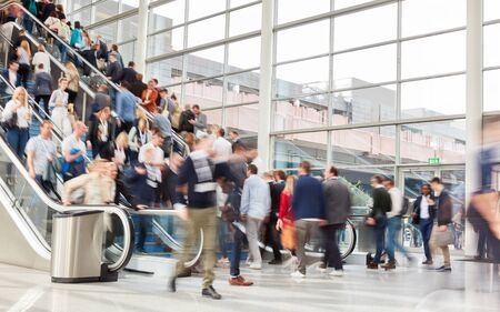 Many anonymous business people on escalator at a trade fair