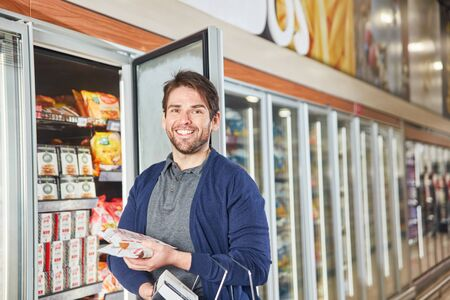 Young man as a consumer at the refrigerated shelf is buying frozen food in the supermarket