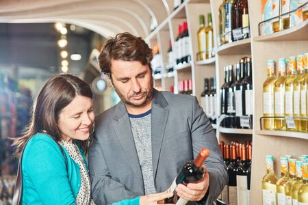 Young couple buying red wine reads label on the bottle in front of the wine rack Standard-Bild