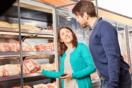 Young couple in front of the freezer in the supermarket choosing the meat variety