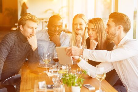 Group at meeting in restaurant looks together on tablet computer