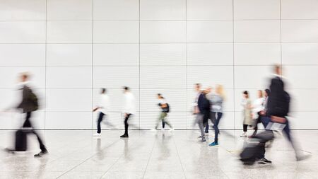 Many anonymous people and business people in a hurry at trade fair or at the airport Stock Photo