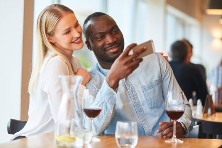 Amorous multicultural couple is taking a selfie while rendezvousing in the restaurant