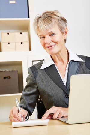 Smiling businesswoman writes with pen on a notepad
