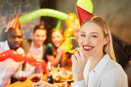 Cheerful woman with a trumpet at a carnival or carnival party with friends Stock Photo