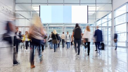 Many anonymous trade fair visitors go along under large advertising space